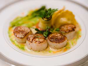 Seared Scallops with Ravioli and Asparagus Plated with light sauce
